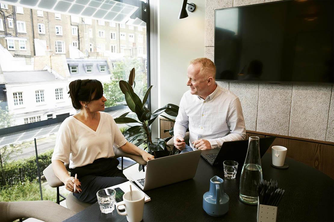 Zwei Personen besprechen Themen rund um Immobilienverwaltung