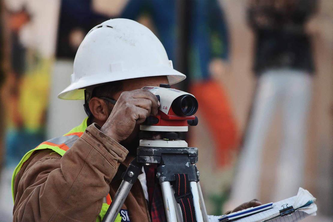 Arbeiter bei Vermessung eines Grundstücks